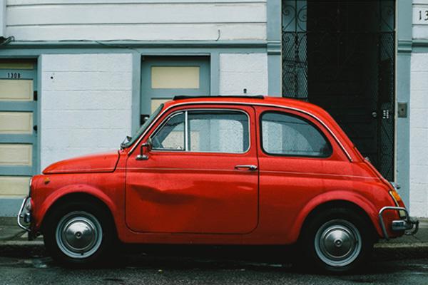 a damaged red rental car