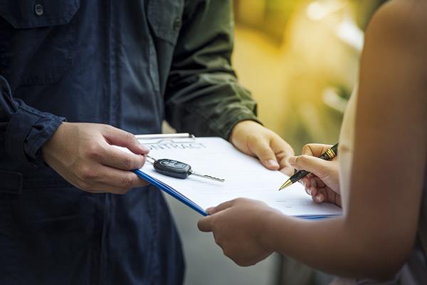 signing car rental agreement